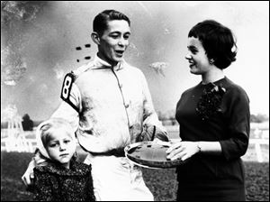 Jeanne Phillips, reigning Miss Toledo, presents an award to jockey Bobby Wall as he stands with young Sue Wankentin on Oct. 27, 1958, at Maumee Downs racetrack.