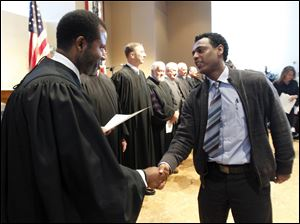 Judge Myron Duhart II congratulates Tesfagebriel Afeworki Mehari, formerly of Eritrea.