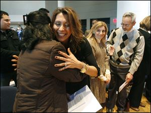 Betty Ubando Frisco, left, formerly of the Philippines, gets a hug from Paola Rebeca Green, formerly of Costa Rica, after taking the Oath of Citizenship at St. Francis de Sales High School.
