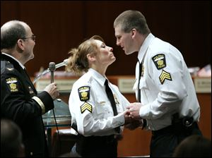 Newly promoted Lt. Kelli Russell receives a kiss and her new lieutenant's badge from her husband, Sgt. Corey Russell, during the Toledo police promotions ceremony while Chief Mike Navarre, left, watches.