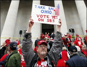 Richard Ringo, a members of The Ohio Liberty Council, a coalition of over 60 tea party groups and liberty minded organizations across Ohio, holds a sign in support of Senate Bill 5 at the Ohio Statehouse on Thursday in Columbus.
