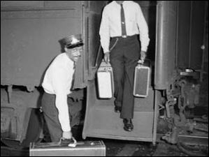 Two members of the Brotherhood of Sleeping Car Porters carry luggage from a sleeping car in this 1946 photo.