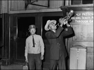 Pennsylvania Railroad Station porter Forrest Waters Sr., wearing badge No.15, holds a suitcase next to a man playing the trumpet. The photo was taken by Charles