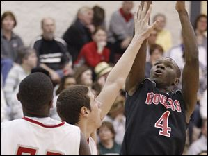 Rogers' Glandoy Hill (4) shoots over Central Catholic's Keith Towbridge (52)  and an Irish teammate.