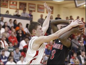 Central Catholic's Andrew Lehman (20) defends against  Rogers' Tony Kynard (3).