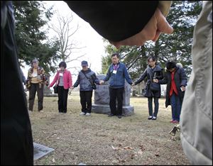 The Rev. Koo Jong Mo, a Seoul pastor, leads prayer at Dr. Horace Newton Allen's grave in Woodlawn Cemetery.