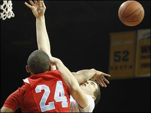 St. John's Jesuit's Trent Brodbeck (34) is blocked by  Bowsher's Mookie Mustafaa (24).