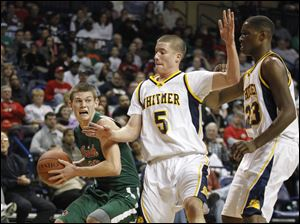 Central Catholic's Andrew Lehman (20) tries to get around Whitmer's Mike Szymanski (5) and Nigel Hayes (23).