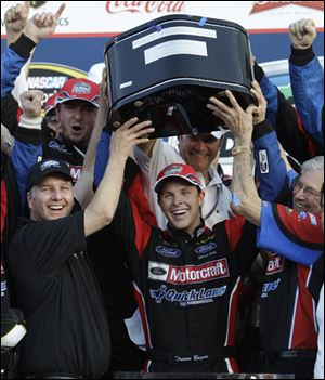 Trevor Bayne, center, holds up the trophy in Victory Lane with help from Eddie Wood, left, and Leonard Wood, right, of Wood Brothers Racing, after winning the NASCAR Daytona 500.