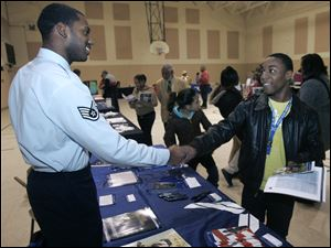 Air Force recruiter Patrick Jefferson, left, shakes hands with Devante Rice, 18, during an after-school college fair at the James C. Caldwell Center in Toledo, Ohio.