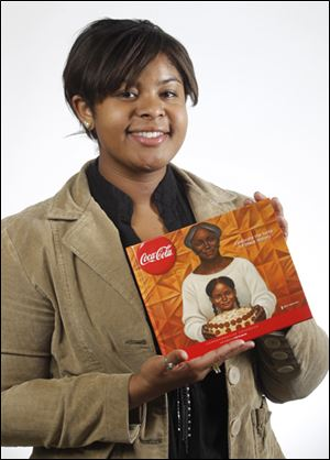 Brooke Campbell with the Coca-Cola cookbook featuring her poetry.