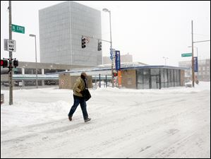 A pedestrian runs across North Erie Street In downtown Toledo.