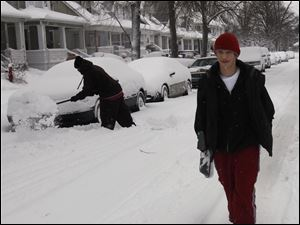 Edward Mockensturm, 14, looks for shoveling jobs on Foraker Avenue in Toledo. About 6 inches of snow coated Toledo overnight, causing schools to be cancelled. He was with his brother Andrew, 17 (not shown).