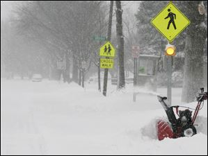 Maumee resident Chuck Tubbs snow blows his Dussel Dr. driveway after nearly 6 inches of snow covered the Toledo area.