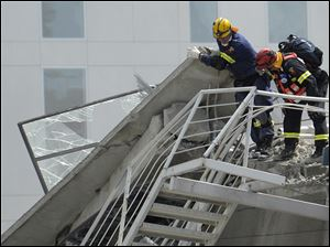 Search and recovery personnel assess possible search access at the destroyed building in Christchurch.
