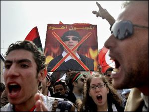 Egyptian protesters chant slogans as they hold an anti-poster of Libyan Leader Moammar Kaddafi during a Friday demonstration in Tahrir Square in Cairo, Egypt.