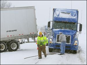 Tow truck driver Kevin Piasecki, wearing a yellow jacket, has his hands full Friday as he prepares to pull a jackknifed semi-trailer truck, left, out of the snow and pull another semi, right, to a less slippery spot on north bound U.S. 23, just south of the Sylvania Monroe Street exit in Sylvania Township. The rig, left, driven by Edward Carder of Delphos, Ohio, (not pictured) slid off the road during the morning snowstorm. The truck at right stopped for the accident and then couldn't move on the ice-covered roadway.