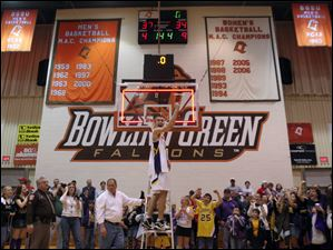 Holgate's Joe Baker cuts a piece of the net at Anderson Arena after his team won the Division IV regional championship game March 16, 2007.