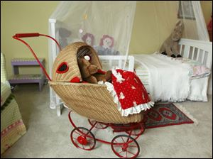 A teddy bear is waiting to be strolled in a wicker baby buggy.