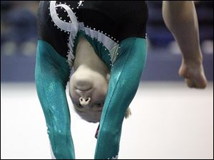 Clay High School bymnast Jody Demeo competes on the beam at the District Gymnastics Tournament.