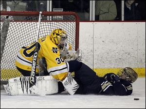 Northview goalie Austin Gryca (30) stops the puck and St. John's player Jake Kennedy.
