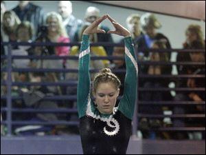 Clay High School gymnast Kylee Ault competes on the beam at the District Gymnastics Tournament.