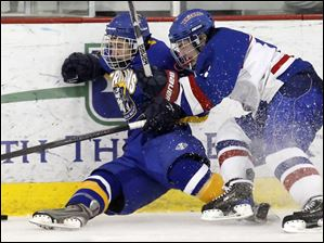 St. Francis' Jake Wawrzyniak, right, and Findlay's Ethan Willis crash into the boards as they chase the puck.