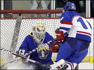 St. Francis' Nate Opblinger (10) slips the puck past Findlay goalie Max Poe.