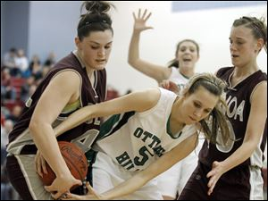 Genoa's Bailee Adams (42) battles Ottawa Hills Nancy Rumpf (5) for the ball. At right is Genoa's Julie Swartzmiller (10).