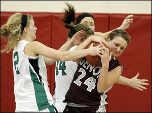 Genoa's Rachel Johnson (24) battles Ottawa Hills' Caroline Arnos (2) for a rebound during a Division III girls sectional basketball game at Bowsher High School in Toledo, Ohio.