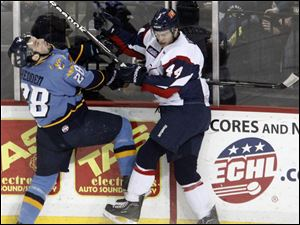 Mike Hedden, left, is smashed into the boards while battling for the puck with Kalamazoo's Mitch Versteeg. After the Walleye fell behind 4-1, they eventually tied it when Hedden scored in the second.