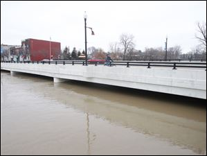 A cyclist rides over the Main Street bridge in Findlay as the rising Blanchard River nears its support beams on Feb. 28, 2011.