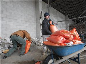 Joe Garza and Kevin Plassman fill a wheelbarrow full of sandbags bound for First Federal Bank in downtown Findlay, which was threatening to flood Feb. 28, 2011.