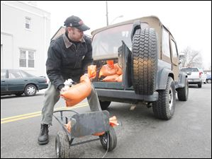 Rob Hizer, of Findlay, fills his Jeep with sandbags that the city made available.
