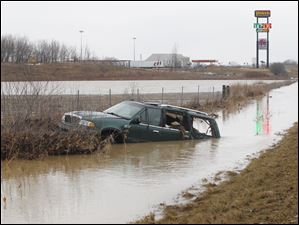 A green SUV is stuck in a water-swollen ditch Feb. 27, 2011, on southbound Interstate 75 just south of State Route 613 near Findlay, Ohio. According to the Ohio Highway Patrol, the driver hydroplaned off of the road into the ditch at about 4 a.m. Monday.  No one was seriously injured.