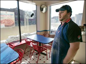 Casey Hensley, general manager of a Domino's Pizza on North Main Street in Findlay, Ohio, stands in his dry restaurant that was shored up with sandbags to prevent flood water from the Blanchard River from entering the business.