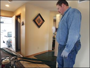 Fritz Kin uses a pump to drain water from a friend's basement at 1522 Hunter's Creek Drive in Findlay.