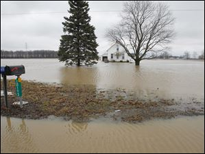 The home at 10193 Hancock County Road 180 in rural Findlay is completely surrounded by flood water.