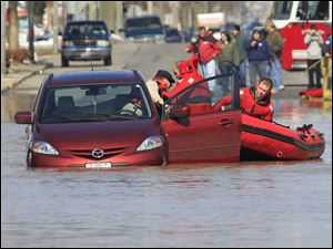 Findlay firefighters pull an unidentified man from his car on flooded North Main Street in Findlay, Ohio, Tuesday, March 1, 2011. The man told firefighters he thought he could make it through the water.