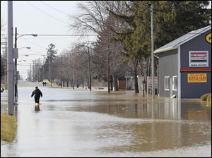 Nick Amador walks through flood water from the Blanchard River on Route 224 in Ottawa, Ohio, Tuesday, March 1, 2011.  He said his basement was flooded and wanted to remove a water heater but had to get a part from a nearby hardware store.