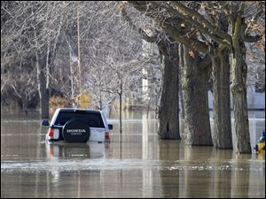 A parked car is submerged in flood water from the Blanchard River on East Third Street near Perry Street in Ottawa, Ohio, Tuesday, March 1, 2011.