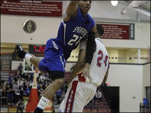 Springfield player Leroy Alexander (24) makes the basket and is fouled by Bowsher player Mookie Mustaffa (24). Alexander poured in a game-high 23 points for the Blue Devils and pulled in 16 rebounds.