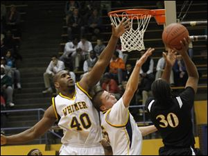 Whitmer's Ken Hayes (40_ and Mike Szymanski put pressure on Start's Maurice Taylor (30).