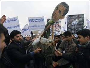An effigy of President Obama is prepared for burning during a protest in Kabul. Hundreds of left-wing political party supporters marched through the city streets Sunday to protest U.S. military operations and demand withdrawal of foreign troops.