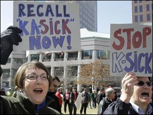 Karen Fitzpatrick, left, and Bill Collins protest Tuesday in Columbus, Ohio. Fitzpatrick , a retired engineer and Collins, a small businessman, are from Cincinnati.