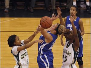 Spartans player Kela McCarver (4) blocks the shot of Anthony Wayne's Emma Ricketts.