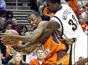 BGSU's Dee Brown fights to get to the basket past the defense of Western Michigan's Flenard Whitfield.