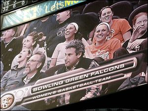 Members of the BGSU women's basketball team appear on the video board as they cheer on the men's team.