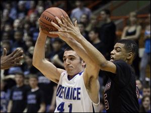 Defiance's Doug Herrett (41) drives past Scott's Chris Harris (5). Herrett would give Defiance 17 points.