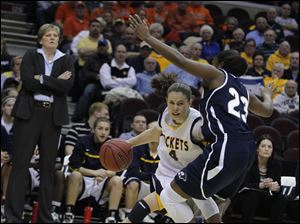 UT's Naama Shafir (4) drives around Akron's Jasmine Mushington (23) as Rockets head coach Tricia Cullop looks on.